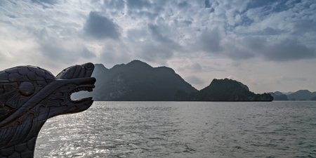 Chinese dragon head wood carving tourist boat travel Halong Bay Tour Cruise Discover Rocky islands spectacular limestone in northern Vietnam. focus on the head
