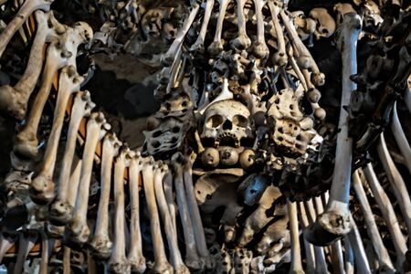 Human Skeleton bones and skulls background. Abstract concept Skeleton grave. Part of interior decorated marble skull and bones church wall hell. Stock Photo