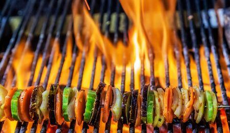 Cocinar asar a la parrilla en parrilla en llamas Kebabs al vapor verduras cortadas mixtas en brochetas Foto de archivo