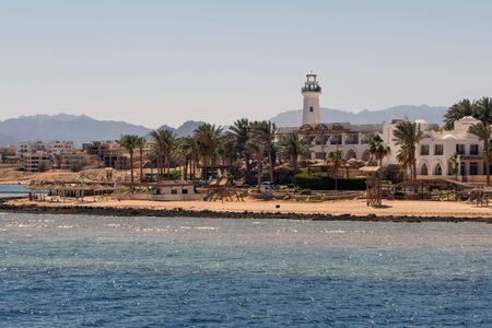 Public sandy beach and lighthouse sea. Chair and umbrella honeymoon vacation panorama Zdjęcie Seryjne