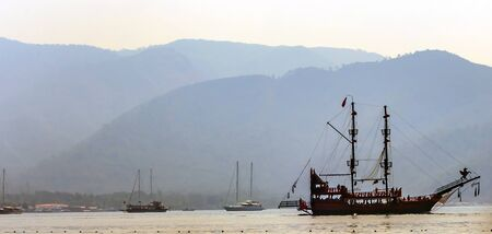 wooden cruise ship in the bay Aegean Sea in Turkey. Turkish coast Rocks hills and mountains.