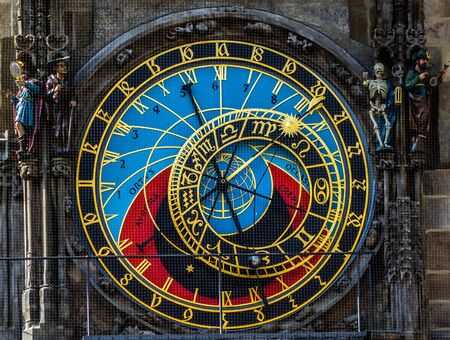Prague Astronomical Clock, or Prague Orloj. the astronomical dial, representing the position of the Sun and Moon in the sky and displaying various astronomical details background. Golden Roman numerals.