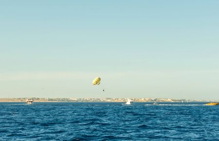 Parasailing over red sea in blue sky with parachute Roped The Motor Boat.