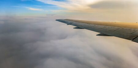 jet airplane flying above clouds in dramatic sunset. Travel fly cruise transportation concept view from airplane window on the wing.