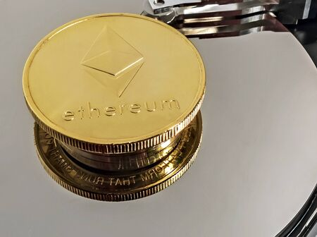 Physical Coin Cryptocurrency Ethereum ETH Gold Plated Bitcoin in laptop hard disk server. Crypto currency blockchain Ethereum Coin virtual money concept isolated on white background.