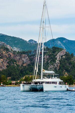 Luxury Sailing catamaran mountains background anchored in a bay Archivio Fotografico