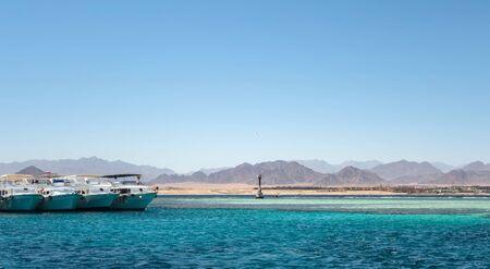 White yachts tourists in Bay Akaba background Red sea and Tiran Kingdom Saudi Arabia, island near Sharm El Sheikh in Egypt