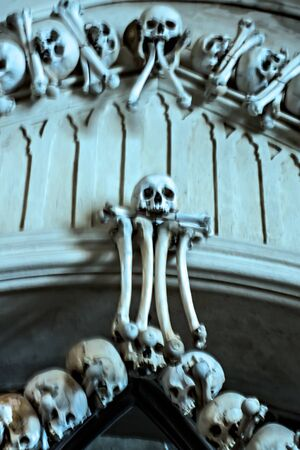 Non focus Blur Design. Human Skeleton bones and skulls background. Abstract concept Skeleton grave. Part of interior decorated marble skull and bones church wall hell. Stock Photo