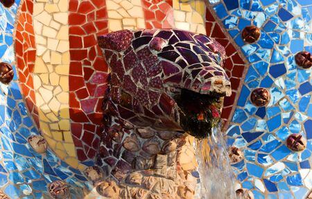 Architectural dragon head detail Designed by Gaudi decoration in Park Guell Beautiful Snake fountain of colored Mosaic Tiles Barcelona. Antoni Gaudi Catalonia, Spain