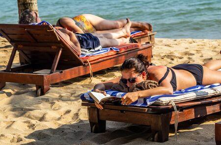 PHAN THIET, VIETNAM - Feb 16, 2015: Girl pretty, People tropical beach with coconut palm trees, Phan Thiet. Sunbed woman tanned body bikini sunbathing on deck chair, relaxing on beach chair. Standard-Bild - 134696780