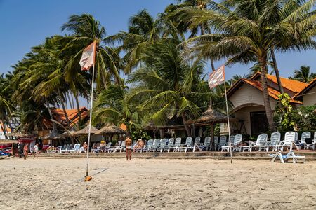 PHAN THIET, VIETNAM - Feb 16, 2015: Girl pretty, People tropical beach with coconut palm trees, Phan Thiet. Sunbed woman tanned body bikini sunbathing on deck chair, relaxing on beach chair. Standard-Bild - 134696824