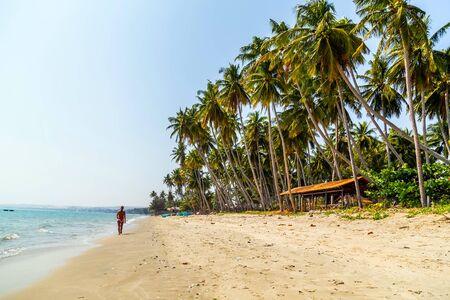 PHAN THIET, VIETNAM - Feb 16, 2015: Girl pretty, People tropical beach with coconut palm trees, Phan Thiet. Sunbed woman tanned body bikini sunbathing on deck chair, relaxing on beach chair. Standard-Bild - 134697040