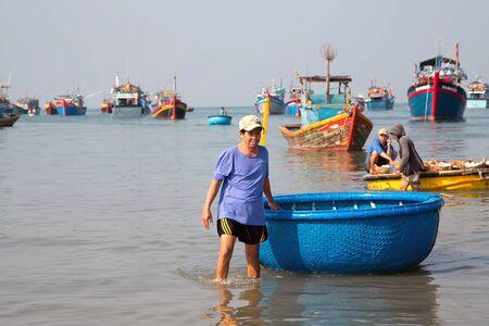PHAN THIET, MUI NE, VIETNAM - 16 de febrero de 2015: Pescador captura barcos vietnamitas. Las personas que trabajan en el muelle de pesca en el pueblo pesquero de Phan Thiet, viajan por la costa del sudeste asiático Binh Thuan de Vietnam.