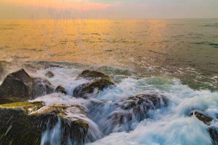Waves are breaking about the breakwater at sunset or sunrise. Storm Kicks ocean background. Abstract background nature blur textures soft focus.