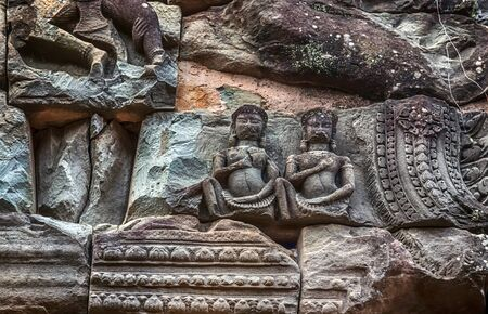 Khmer architecture Detailed carvings on the pink limestone walls of Banteay Srei temple Bas-reliefs are individual figures jungles of ruins Angkor near Angkor wat Siem Reap Cambodia