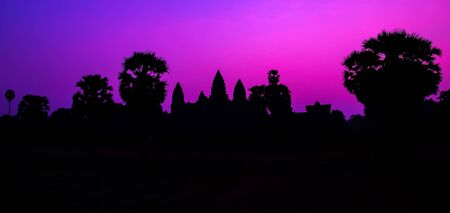 Panorama Mist sunrise morning violet mauve colorful sky landscape. Famous facade silhouette of Cambodian ancient temple Angkor wat, Angkor Archaeological Park near Siem Reap in Cambodia. Palm trees Stock Photo