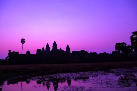 Beautiful Purple colorful sunrise at lake holy Angkor Wat facade silhouette, famous destination in Cambodia. Angkor Archaeological Park near Siem Reap in Cambodia.