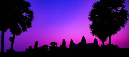 Sunrise Purple ancient temple facade silhouette Palm trees the Angkor Wat temple in Angkor Archaeological Park near Siem Reap in Cambodia.