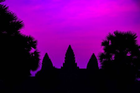 Silhouette of Cambodian ancient temple Angkor wat, Angkor Archaeological Park near Siem Reap in Cambodia. Panorama Mist sunrise tropical morning violet mauve colorful sky landscape Palm trees.