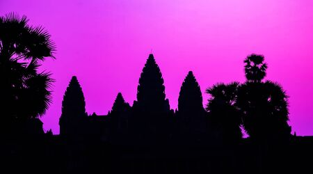 Panorama Mist sunrise tropical morning violet mauve colorful sky landscape. Palm trees silhouette of Cambodian ancient temple Angkor wat, Angkor Archaeological Park near Siem Reap in Cambodia.