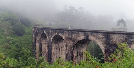 Morning mist in Nine Arch Bridge Railway Viaduct in Ceylon, Demodara - Tourist attractions in Badulla District, Sri Lanka. Stock Photo