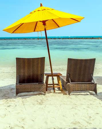 Two Lounge Chairs and Yellow Umbrella at white sandy beach, Phuket, Thailand. Stockfoto