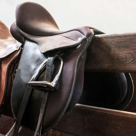 Leather saddle hanging horses with Horse Riding equipment stirrups horseback Close up isolated on white background