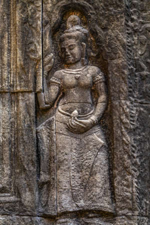 Apsara Khmer dance Stone Carving Sculpture on the wall. Relief of devata at Angkor Wat temple facade carving. Siam Reap Cambodia in Angkor Wat complex.