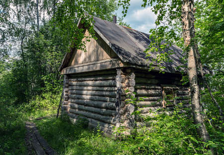 Weathered exterior wooden sauna of ancient log cabin shelter in the forest Natural backgrounds Stockfoto