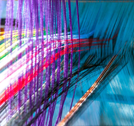 Colored threads cotton weaving on manual wooden loom. National Handloom Day.