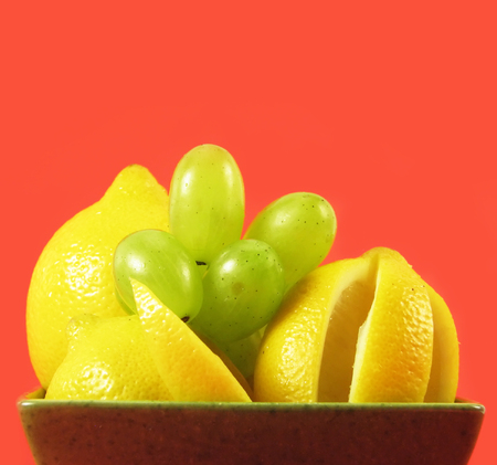 lemon and grape in green bowl in green bowl on red background photo