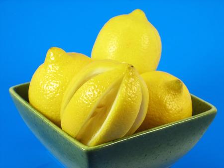 citrus fruits: lemons in green bowl on blue background Standard-Bild