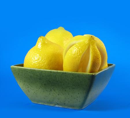 citrus fruits: lemons in green bowl on blue background photo