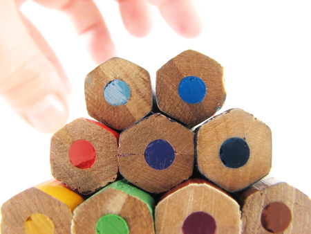 school and office articles: coloured pencils and fingers on white background