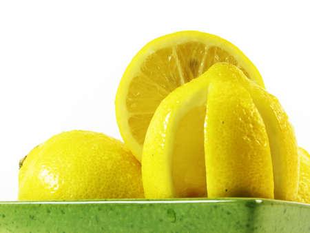 lemon in green bowl in green bowl on white background photo