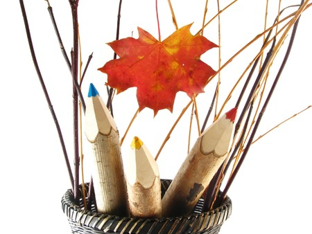 autumn composition with leaf: coloured pencils in basket on white background