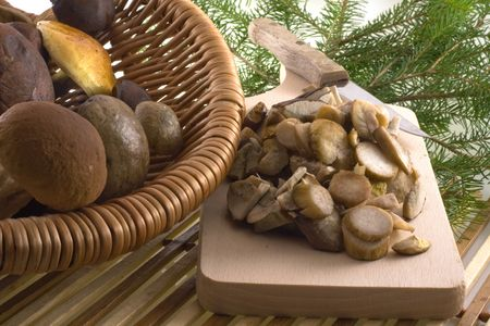 autumn composition: some color mushrooms in basket and on plank Standard-Bild