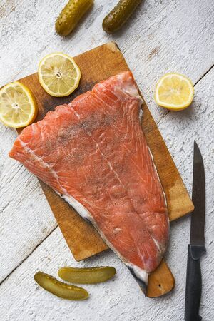 Salmon raw fish on chopping board on white wooden background photo