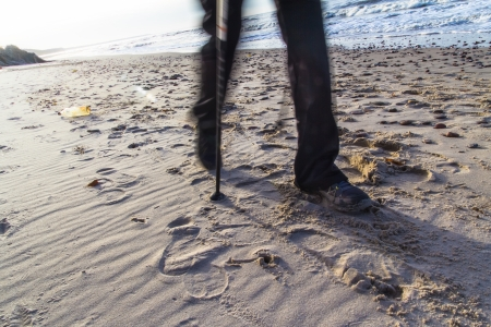 Feet of man cultivating Nordic walking on the beach photo