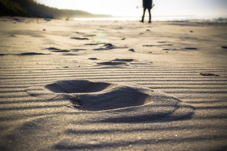 Footprint in the sand and the figure of a man cultivating Nordic walking photo