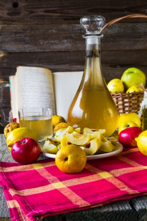 tincture: Tincture of quince and fruit on a wooden table