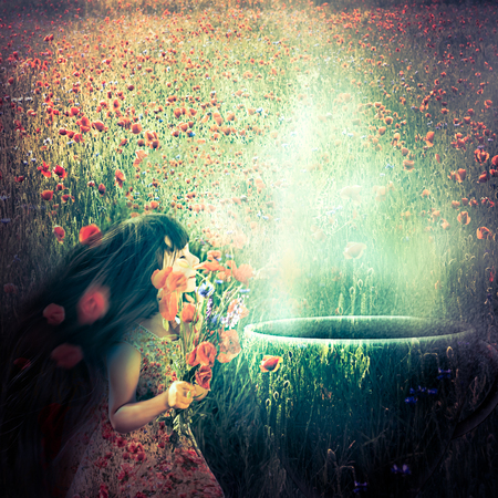 Little girl on an enchanted poppy meadow smelling aroma from a magical cup photo