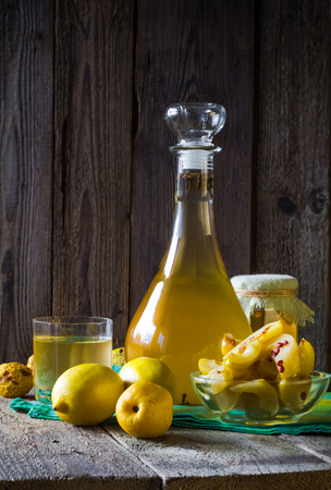 Tincture of quince and fruit on a wooden table