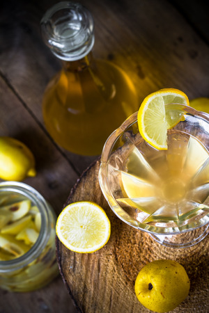 tincture: Tincture of quince cups. Fruits in a jar, lemon and carafe. Stock Photo