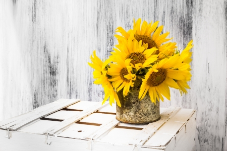 Still life with sunflowers bouquet on matalic rusty cup on white wooden background