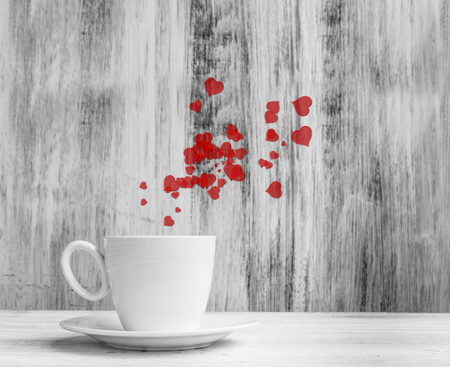 Mug for lovers. White cup full of warm hearts on a wooden background. photo