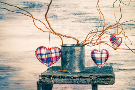Three hearts hanging on the branches in the can