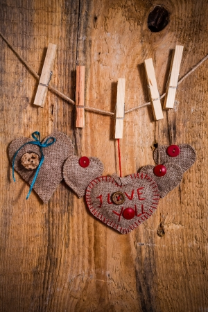 Valentine background with hand-sewn heart with woer I love You on wooden background photo