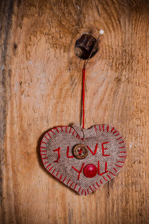 Valentine background with hand-sewn heart with word I love You on wooden background photo