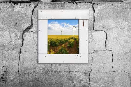 chapped: Old cracked wall with a view of the landscape with windmills Stock Photo